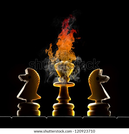 Chessmen (king and two horses). King burns on a black background. - stock photo