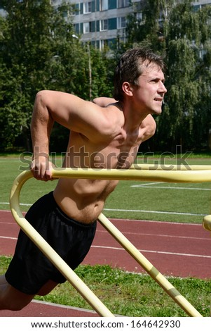 Chest dip on athletic workout at the stadium - stock photo