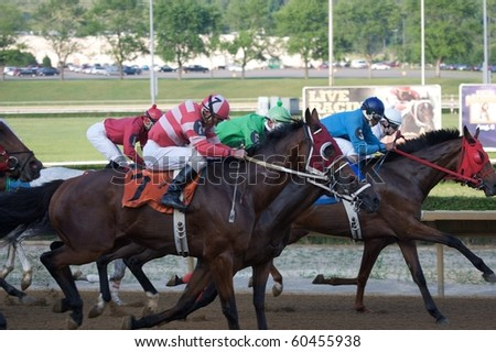 CHESTER, WEST VIRGINIA - JUNE 14: Race horses head down the stretch at The Mountaineer Racetrack on June 14, 2010 in Chester West Virginia. - stock photo