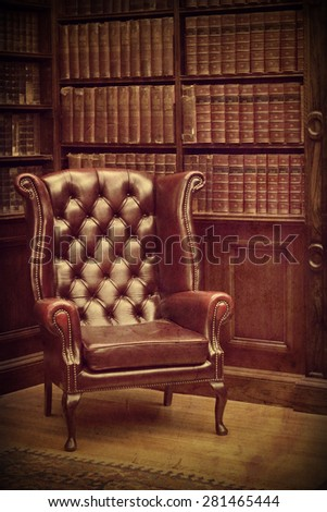 Chesterfield leather armchair in classical library vintage style. Traditional British retro study room