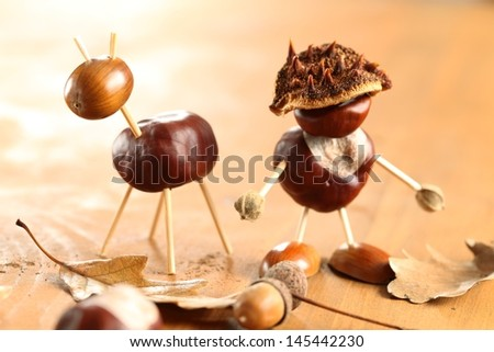 Chestnut and acorn figurines on wooden table. Selective focus, shallow DOF. - stock photo