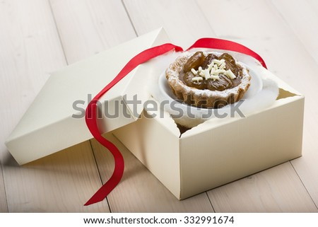 chestnut cake decorated with white chocolate on gift box - stock photo
