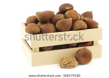chestnuts and a peeled one in a wooden box on a white background - stock photo