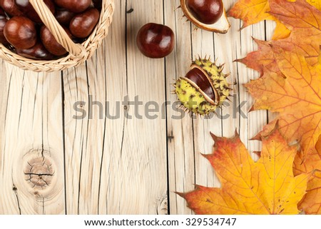 Chestnuts and yellow maple leaves on wooden background
