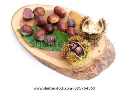 Chestnuts on green leaves and wood - isolated on white                     - stock photo