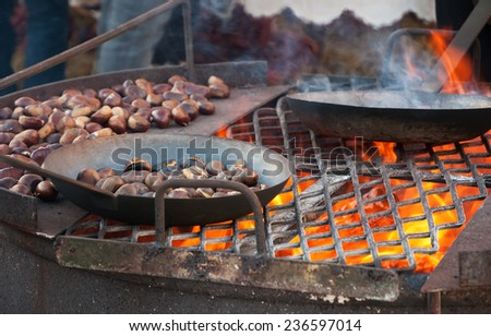 Chestnuts roasted in old iron pans over the fire at traditional Christmas medieval fair in Provins (France). Selected focus on the grill and on the burned chestnuts in the pan. - stock photo