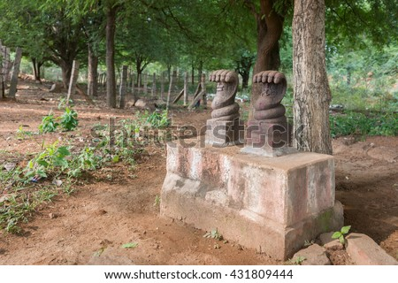Chettinad, India - October 17, 2013: Base holds two large five headed cobra statues in a Lord Shiva forest shrine near Kothamangalam. Foreground brown dirt. Background green forest. - stock photo