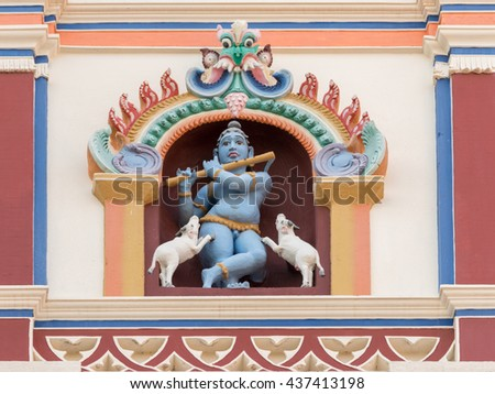 Chettinad, India - October 17, 2013: Chidambara Palace in Kadiapatti. Blue Krishna playing flute and dancing goats statue on front facade. Set in framed niche. - stock photo