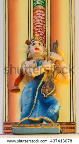 Chettinad, India - October 17, 2013: Chidambara Palace in Kadiapatti. Statue of Veena playing topless woman with blue sari in dance hall. Multi colored warm background. - stock photo