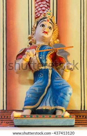 Chettinad, India - October 17, 2013: Chidambara Palace in Kadiapatti. Statue of violin playing woman with blue sari in dance hall. Multi colored warm background. - stock photo