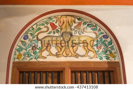 Chettinad, India - October 17, 2013: Chidambara Palace in Kadiapatti. Wall painting above door showing the bodies of four monkeys all leading to one common head. - stock photo