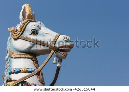 Chettinad, India - October 16, 2013: Decorated head of Ayyanar white horse against blue skies. Ayyanar is the village protector, here the Kadiapatti village. - stock photo