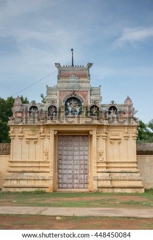Chettinad, India - October 18, 2013: Entrance to Nagar Soorakudi Sundesaswar Meenakshi Ambal Temple. Yellow wall and gate decorated with statues. - stock photo