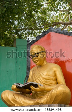 Chettinad, India - October 17, 2013: Golden statue of the actor and politician C.N Annadurai in the Karaikudi City. He reads a book and has black rimmed glasses. Green background. - stock photo