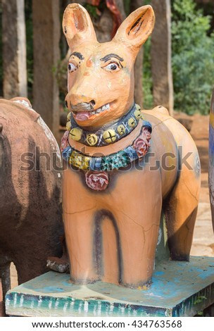 Chettinad, India - October 17, 2013: Kothamangalam Ayyanar horse shrine. An exception in the line of clay horses, this orange clay dog smiles and is attentive.  - stock photo
