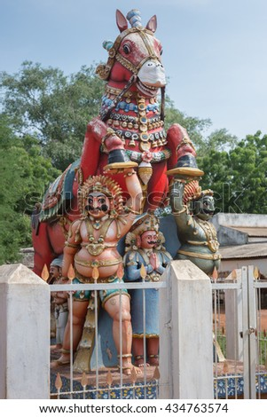 Chettinad, India - October 17, 2013: Kothamangalam Ayyanar horse shrine. Ayyanar in white and black avatars and supporting his red horse. Figure between them is sponsor of statue. - stock photo
