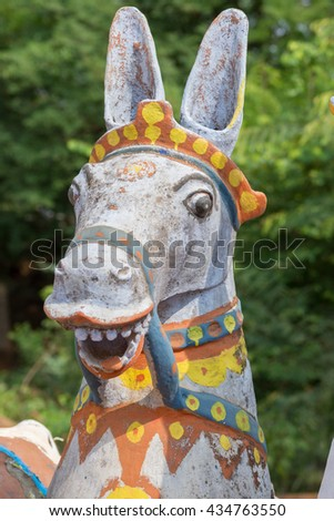 Chettinad, India - October 17, 2013: Kothamangalam Ayyanar horse shrine. Focus on the head of one laughing white horse with red and yellow trim.  - stock photo