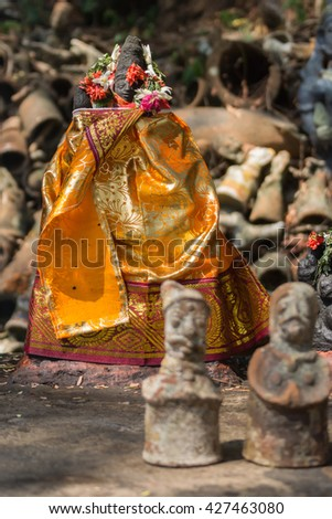 Chettinad, India - October 16, 2013: Orange robed Ayyanar, village protector, shrine of Namunasamudran. Clay male and female figurines are offered to influence the gender of the child during pregnancy - stock photo
