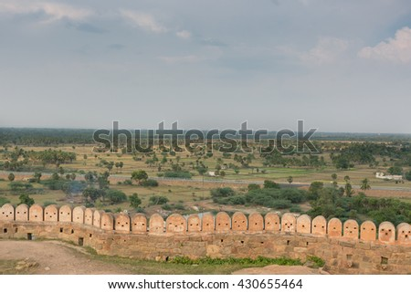 Chettinad, India - October 16, 2013: View on the surrounding region of Thirumayam Fort. Ramparts and battlements in foreground. Battlements look like robot faces. - stock photo