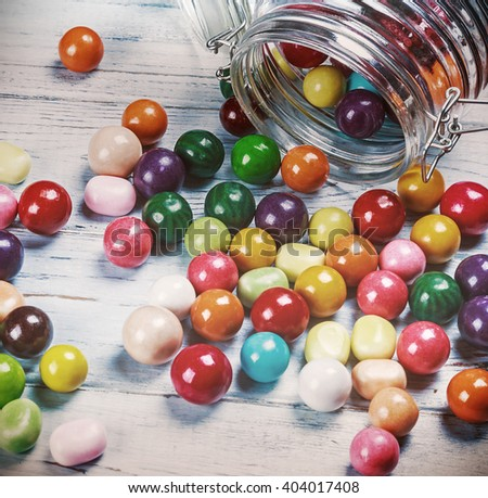 chewing gum and candies in jar on wooden background. focus on sweets and a glass jar. Toned image - stock photo