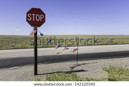 Cheyenne, Kansas, USA. View across endless prairie long Inter state 25 in late summer with stop sign and American flag between Douglas and Cheyenne, Kansas, USA.