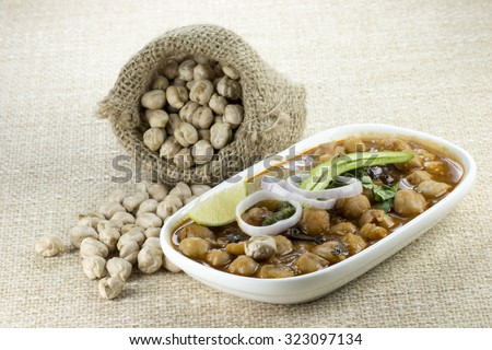 Chhole / Chickpea / Bengal gram / Garbanzo raw and cooked. (a delicious spicy snack with green chillies, sliced onions, coriander leaves and lemon.) - stock photo