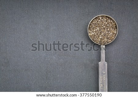 chia seed on metal measuring tablespoon against slate sone with a copy space
