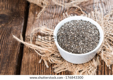 Chia Seeds in a small bowl (on dark wooden background) - stock photo