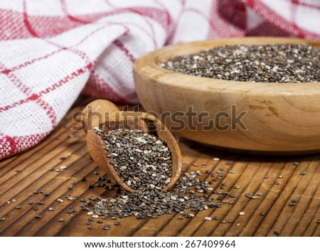 Chia seeds in wooden bowl and spoon on wooden background. - stock photo