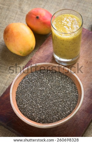 Chia seeds (lat. Salvia hispanica) in bowl with mango and chia juice in the back photographed with natural light. Chia seed is considered a superfood (Selective Focus, Focus in the middle of the bowl) - stock photo
