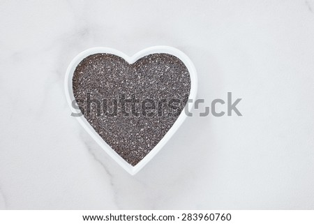 Chia seeds. Raw whole  chia seeds in a hearts shaped dish. Natural light - stock photo
