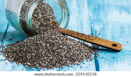 Chia seeds with wooden spoon on blue background, selective focus - stock photo