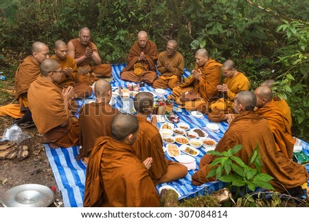 CHIANG DAO, THAILAND, JANUARY 06, 2015: Group of Buddhist monks praying for new year celebration before an outdoor lunch in the foggy wild nature of the Chiang Dao mount in Thailand. - stock photo