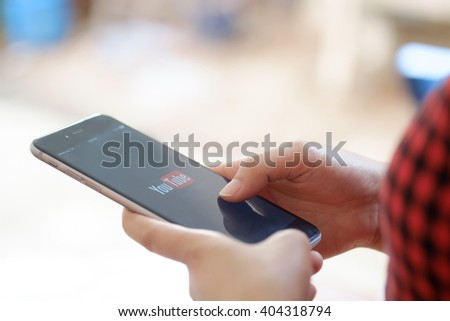 CHIANG MAI, THAILAND - APR 12 2016: : Brand new Apple iPhone 6 plus with YouTube app on the screen lying on old wood desk with headphones. YouTube is the popular online video sharing website - stock photo