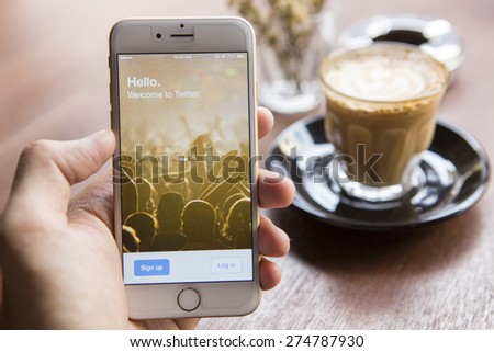 CHIANG MAI, THAILAND - APRIL 22, 2015: A man trying to log in Twitter application using Apple iPhone 6 in coffee shop. Twitter is largest and most popular social networking site in the world. - stock photo
