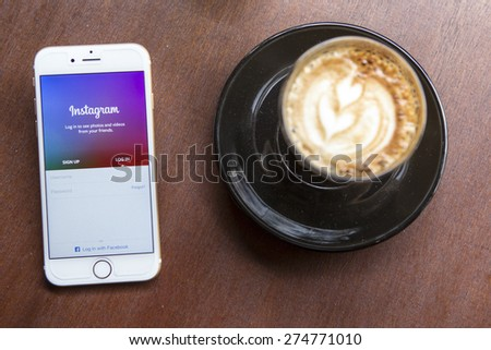 CHIANG MAI, THAILAND - APRIL 22, 2015: Instagram application using Apple iPhone 6 on coffee shop table. Instagram is largest and most popular photograph social networking site in the world. - stock photo