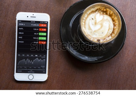 CHIANG MAI, THAILAND - APRIL 22, 2015: iPhone 6 with application Stocks of Apple on the screen in coffee shop cafe. iPhone 6 was created and developed by the Apple inc. - stock photo
