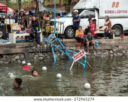 CHIANG MAI, THAILAND - APRIL 13 2015: Locals swim in the dirty moat water at Songkran (Thai New Year Celebration). The annual water festival in Chiang Mai City, Northern Thailand. - stock photo