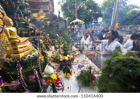 CHIANG MAI  THAILAND - AUGUST 12 :Buddhist metal cast ceremony for buddha statue , Throw flower petal  on altar in metal cast ceremony . Aug 12,2012 in Lok Molee Temple, Chiangmai, Thailand. - stock photo