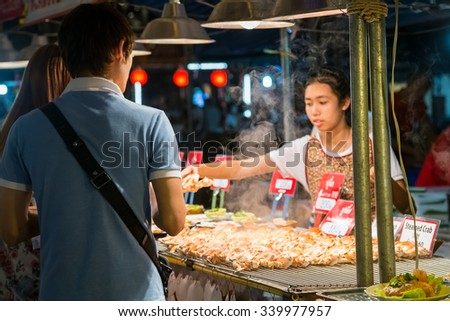 CHIANG MAI, THAILAND - CIRCA AUGUST 2015: Local people sell traditional Thai food and drinks at night market in Chiang Mai, Thailand