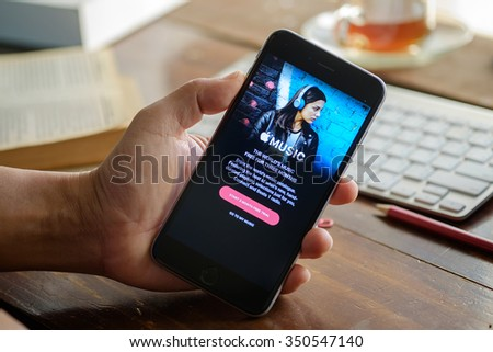 CHIANG MAI,THAILAND - DEC 13,2015:A man hand holding screen shot of Apple music app showing on iPhone 6 plus. Apple Music is the new iTunes-based music streaming service that arrived on iPhone. - stock photo