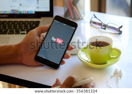 CHIANG MAI,THAILAND DEC 30 - 2015 : Brand new Apple iPhone 6 plus with YouTube app on the screen lying on old wood desk with headphones. YouTube is the popular online video sharing website  - stock photo