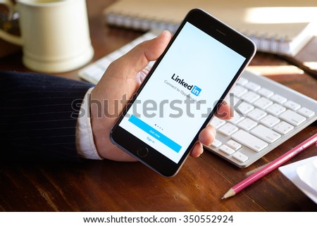 CHIANG MAI,THAILAND - DEC 13,2015:Businessman holding a iPhone 6 plus with social network service LinkedIn on the screen. iPhone 6 was created and developed by the Apple inc.  - stock photo