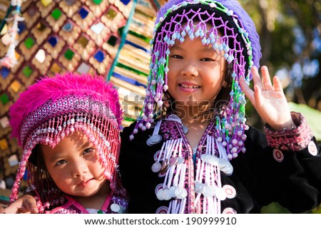 CHIANG MAI, THAILAND - DEC 24: Two unidentified Akha children pose for tourist photos at Wat Phratat Doi Suthep on December 24, 2010 in Chiang Mai, Thailand. - stock photo