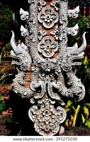 Chiang Mai,Thailand - December 23, 2012:   Detail of carved double dragons on a column in front of the Vihan at Wat Lok Molee *