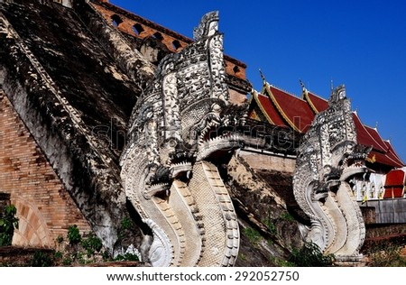 Chiang Mai, Thailand - December 27, 2012:  Two immense carved Naga mythical dragons flank a stairway at historic Wat Chedi Luang dating to 1401