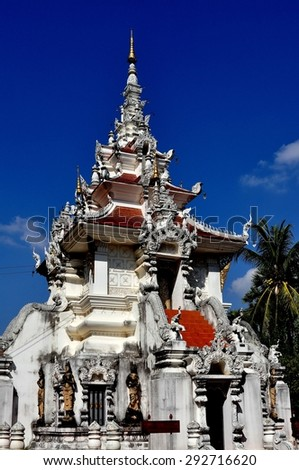 Chiang Mai, Thailand - December 25, 2012:  White pagoda with carved elephants and decorations at Wat Nantaran