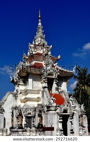 Chiang Mai, Thailand - December 25, 2012:  White pagoda with carved elephants and decorations at Wat Nantaran - stock photo