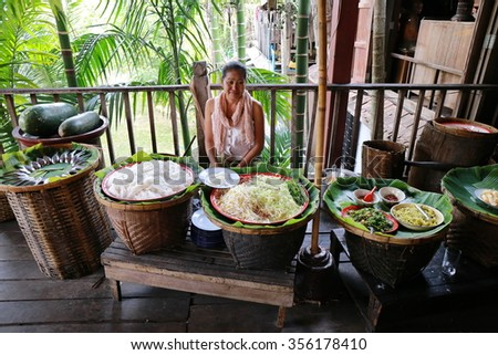 CHIANG MAI, THAILAND - FEB 13: A woman serves Thai food at ancient  market on February 13, 2015 in Chiang Mai, Thailand. Its popular for traditional style food and old Thai culture. - stock photo