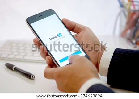 CHIANG MAI ,THAILAND FEB 10 2016 : Businessman holding a iPhone 6 plus with social network service LinkedIn on the screen. iPhone 6 was created and developed by the Apple inc. - stock photo